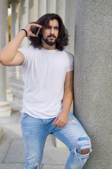 Młody człowiek z długimi włosami, opierając się na kolumnie rozmawia przez telefon