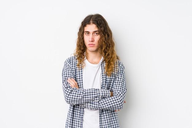 Młody człowiek z długimi włosami pozowanie na białym tle niezadowolony patrząc w kamerę z sarkastycznym wyrazem.