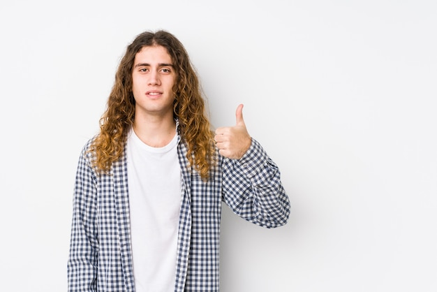 Młody człowiek z długimi włosami pozowanie na białym tle, uśmiechając się i podnosząc kciuk