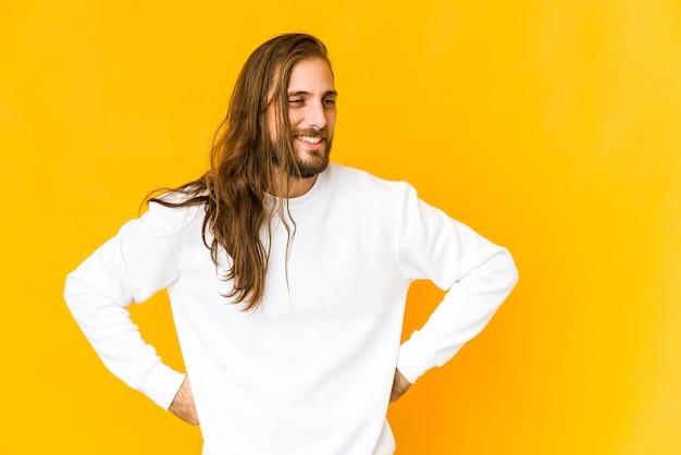 Młody człowiek z długimi włosami śmieje się radośnie i dobrze się bawi trzymając ręce na brzuchu.