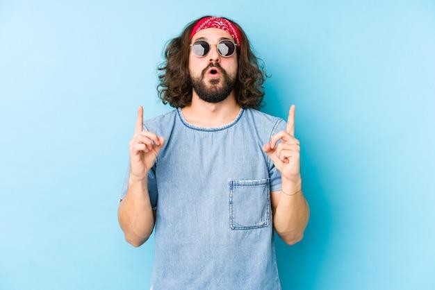 Młody człowiek z długimi włosami sobie wygląd hipster festiwalu na białym tle, wskazując do góry z otwartymi ustami.