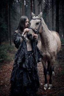 Młody człowiek z długimi włosami z koniem w ciemnym lesie.