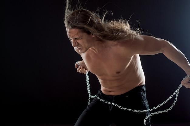 Młody człowiek z długimi włosami zrywa żelazny łańcuch.