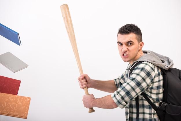 Młody człowiek z drewnianym kijem bejsbolowym i książkami.