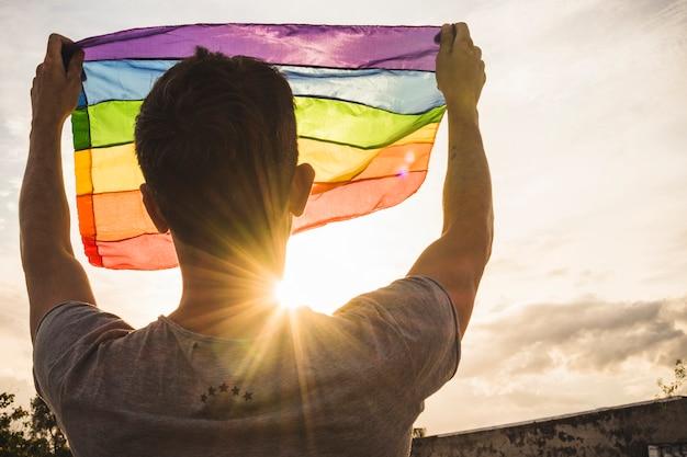 Młody człowiek z dużą flaga w lgbt kolorach i niebie z światłem słonecznym