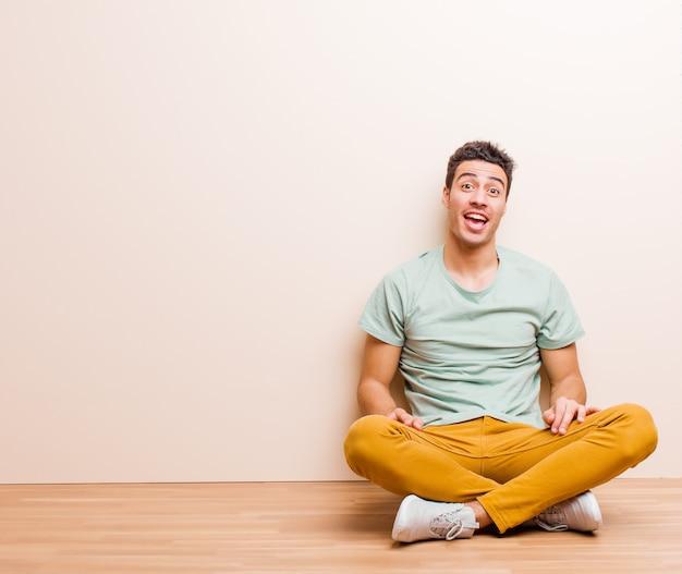 Młody człowiek z dużym, przyjaznym, beztroskim uśmiechem, wyglądający pozytywnie, zrelaksowany i szczęśliwy, relaksujący, siedząc na podłodze