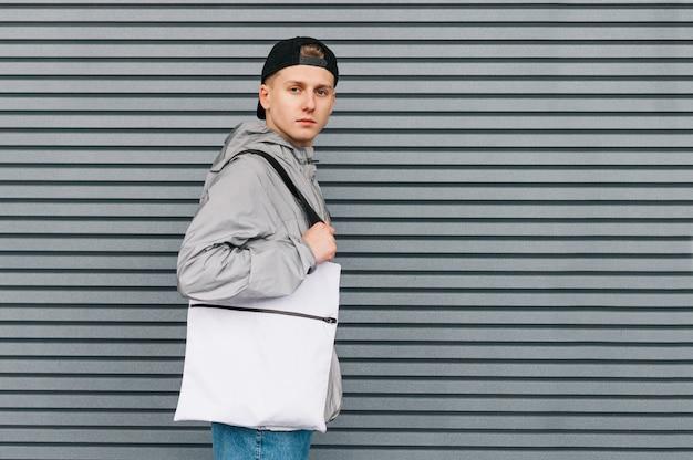 Młody człowiek z ekologiczną torbą na zakupy w rękach z uśmiechem na twarzy, ubrany w stylowe, codzienne ubrania uliczne