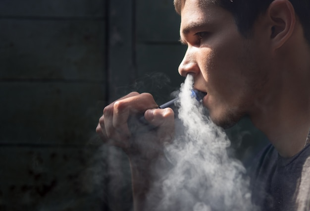 Młody człowiek z elektronicznym papierosem