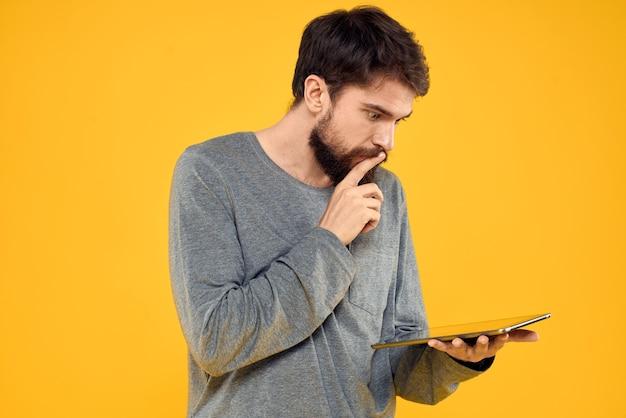 Młody człowiek z elektronicznym tabletem w jego rękach pozowanie