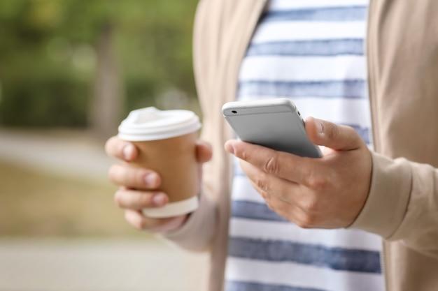 Młody człowiek z filiżanką kawy na zewnątrz swojego telefonu komórkowego