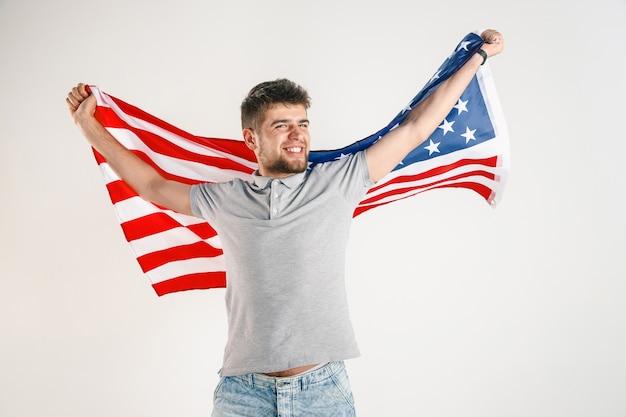 Młody człowiek z flagą stanów zjednoczonych ameryki na białym tle na białym studio.