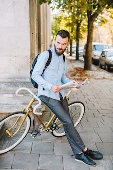Młody człowiek z gazetą opiera na rowerze
