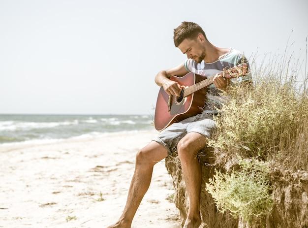 Młody człowiek z gitarą akustyczną na plaży