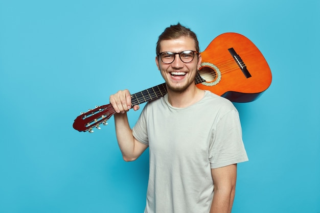 Młody człowiek z gitarą akustyczną na ramieniu, uśmiechając się na niebieskiej ścianie
