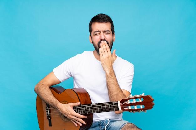 Młody człowiek z gitarą na pojedyncze niebieskie ziewanie i obejmujące szeroko otwarte usta ręką