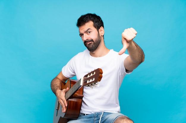 Młody człowiek z gitarą nad odosobnioną błękit ścianą pokazuje kciuka puszek z negatywnym wyrażeniem