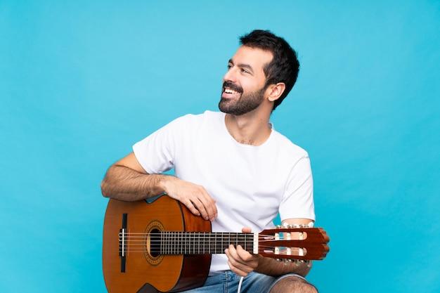 Młody człowiek z gitarą nad odosobnioną błękit ścianą szczęśliwą i uśmiechniętą