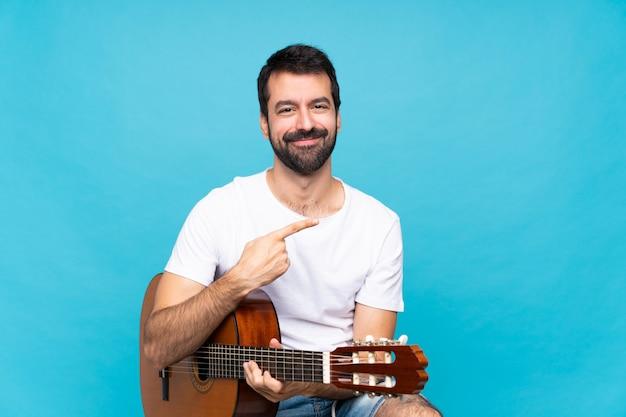 Młody człowiek z gitarą nad odosobnioną błękit ścianą wskazuje z boku przedstawiać produkt