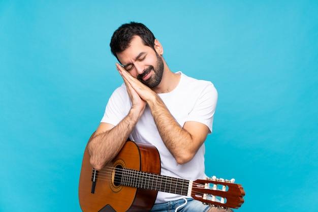 Młody człowiek z gitarą nad odosobnionym błękitnym tłem robi sen gestowi w dorable wyrażeniu
