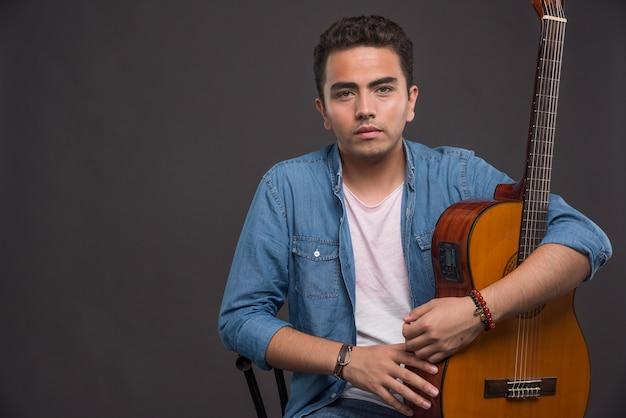 Młody człowiek z gitarą patrząc poważnie na ciemnym tle.
