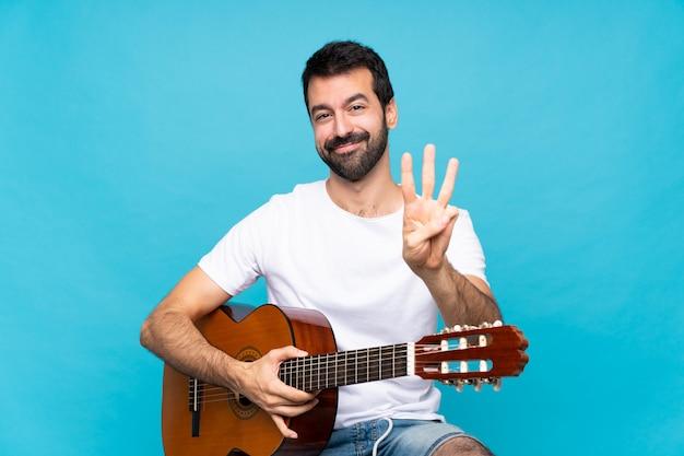 Młody człowiek z gitarą szczęśliwy i licząc trzy z palcami