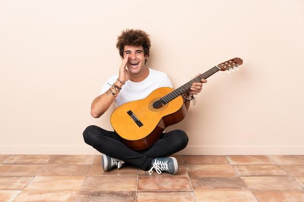 Młody człowiek z gitary obsiadaniem na podłoga