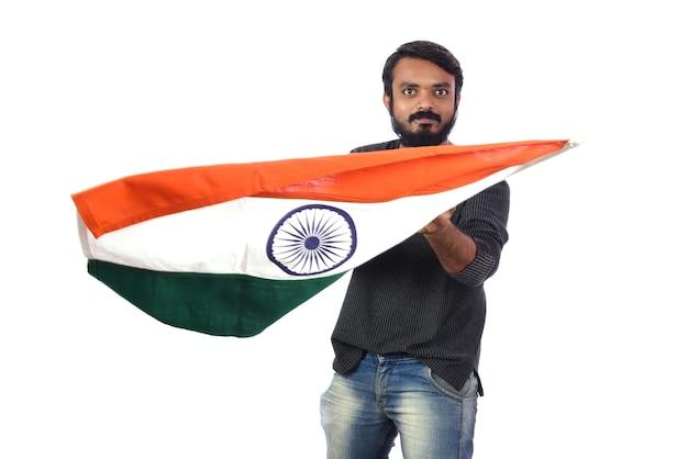 Młody człowiek z indyjską flagą lub tricolor na białym tle