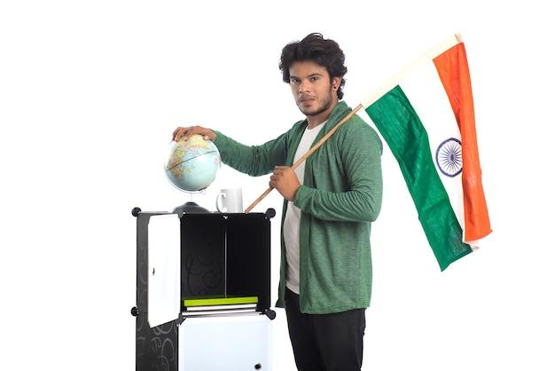 Młody człowiek z indyjską flagą lub tricolor z kulą ziemską na białym tle