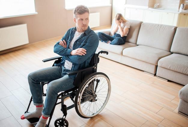 Młody człowiek z inkluzywnością i niepełnosprawnością siedzi na wózku inwalidzkim z przodu. ręce skrzyżowane i zdenerwowane. młoda kobieta siedzieć za na kanapie i płakać. choroba emocjonalna i stres.