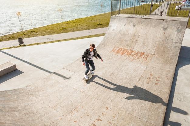 Młody człowiek z jego jeździć na deskorolce w skate parku