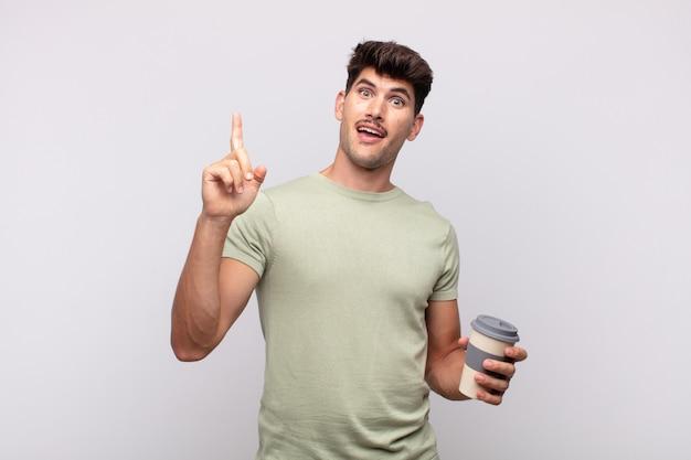 Młody człowiek z kawą czujący się jak szczęśliwy i podekscytowany geniusz po zrealizowaniu pomysłu, radośnie podnosząc palec, eureka!