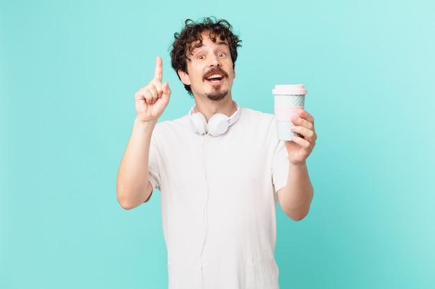 Młody człowiek z kawą czuje się jak szczęśliwy i podekscytowany geniusz po zrealizowaniu pomysłu