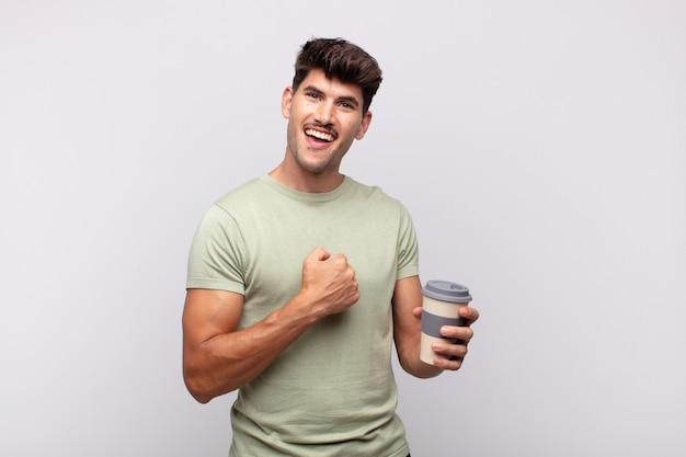 Młody człowiek z kawą czuje się szczęśliwy