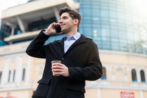 Młody człowiek z kawą iść chodzić po ulicy i używać jego smartphone