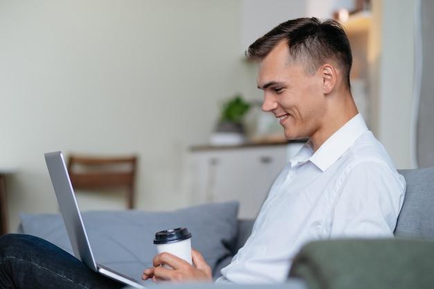 Młody człowiek z kawą na wynos czyta jego e-mail. ludzie i technologia.