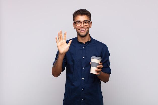 Młody człowiek z kawą, uśmiechnięty i wyglądający przyjaźnie, pokazujący numer pięć lub piąty z ręką do przodu, odliczający w dół