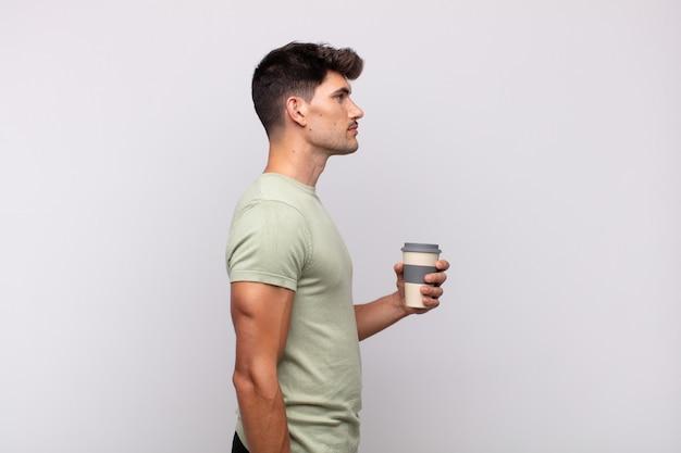 Młody człowiek z kawą w widoku profilu, który chce skopiować przestrzeń do przodu, myśląc, wyobrażając sobie lub marząc