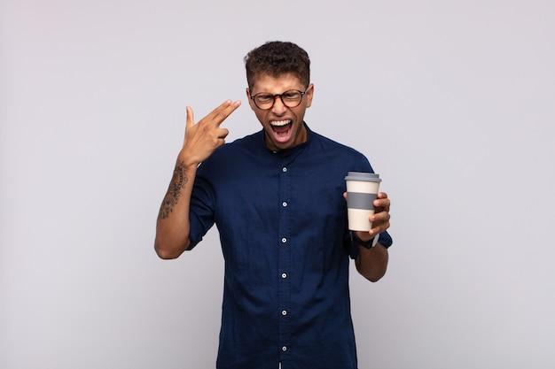 Młody człowiek z kawą wyglądający na nieszczęśliwego i zestresowanego, samobójczy gest robiąc znak pistoletu ręką, wskazując na głowę