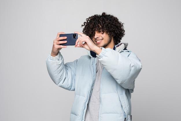 Młody człowiek z kędzierzawym włosy używać telefon komórkowego nad odosobnioną biel ścianą