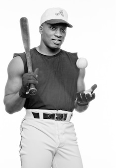 Młody człowiek z kijem baseballowym i piłką, uśmiechając się, portret (b & w)