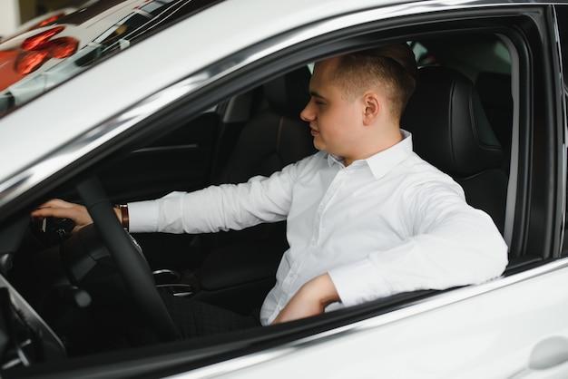 Młody człowiek z kluczami w samochodzie