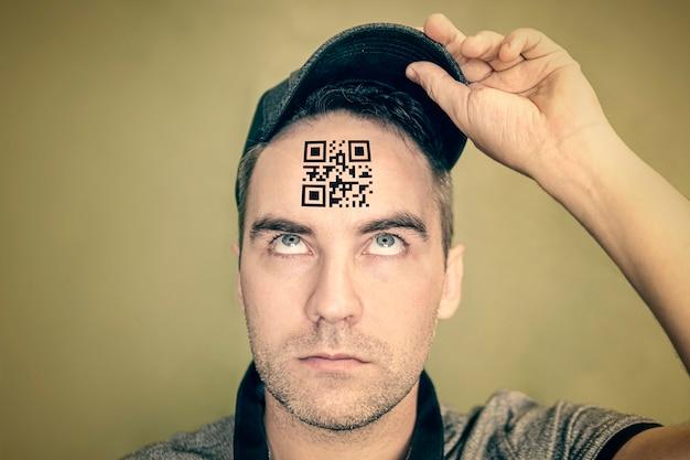 Młody człowiek z kodem qr na czole. mężczyzna o głupim wyrazie twarzy patrzy na swój kod qr na głowie. pojęcie rozdrobnienia populacji. globalna kontrola i zarządzanie
