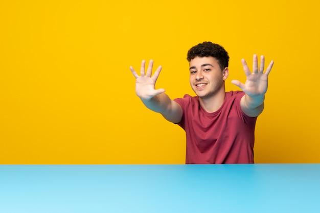 Młody człowiek z kolorową ścianą i stołem liczy dziesięć z palcami
