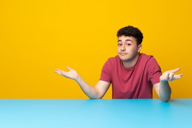 Młody człowiek z kolorową ścianą i stołem ma wątpliwości podczas gdy podnoszący rękę