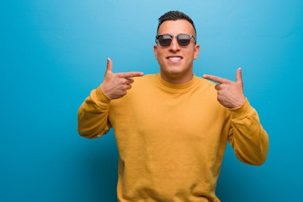 Młody człowiek z kolumbii uśmiecha się, wskazując usta