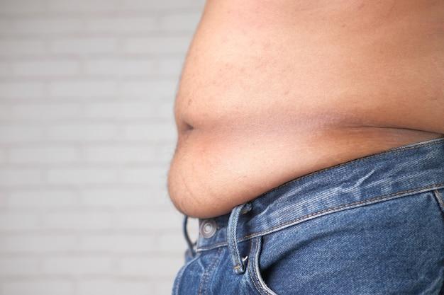 Młody człowiek z koncepcją nadwagi nadmiernego tłuszczu z brzucha