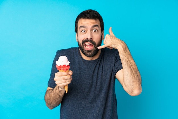 Młody człowiek z kornetem lody nad odosobnioną błękit ścianą robi telefonowi gestykulować i wątpić