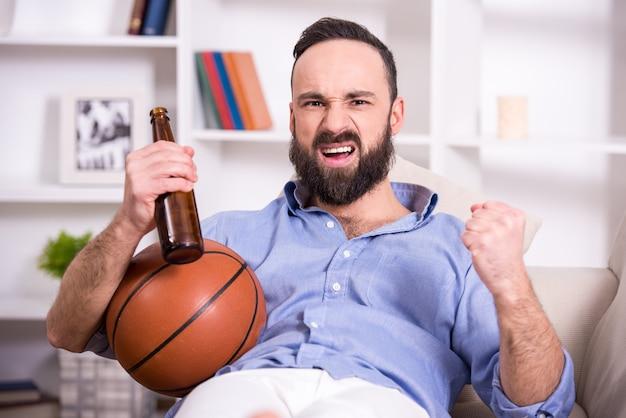 Młody człowiek z koszykową piłką i piwem ogląda grę.