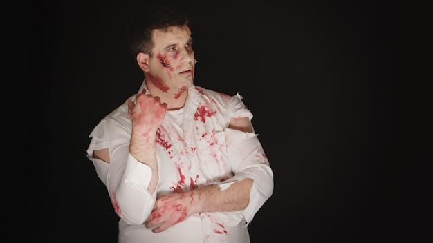 Młody człowiek z krwią na twarzy przebrany za zombie na halloween.