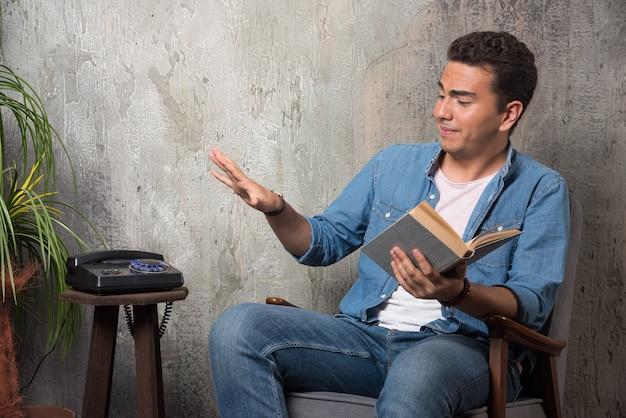 Młody człowiek z książką siedzi na krześle na tle marmuru. wysokiej jakości zdjęcie